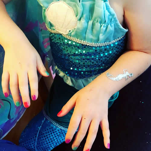 Girl with painted nails and glitter tattoos