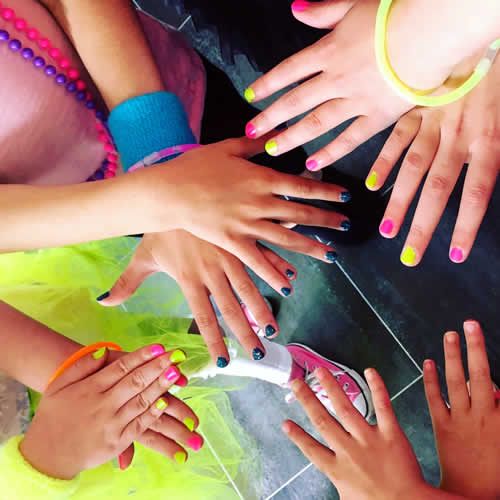 Many pairs of hands with bright neon nails