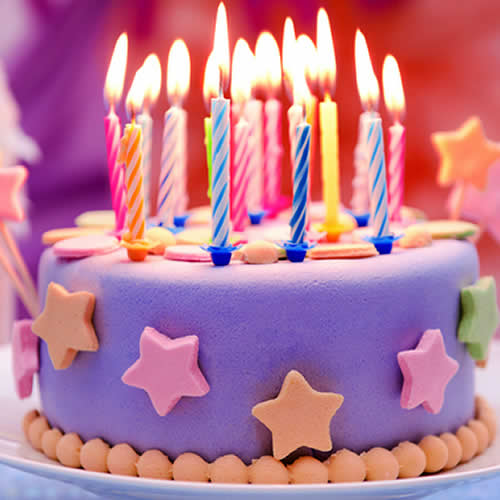 Brightly coloured birthday cake with lit candles